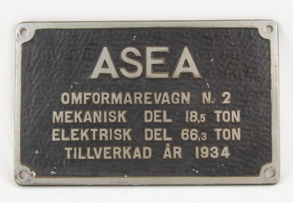 """Skylt till omformarevagn. Rektangulär skylt med rundade hörn och svart skrovlig bakgrund med utstående och omålad text och ram. Text på skylten: """"ASEA OMFORMAREVAGN N. 2 MEKANISK DEL 18,5 TON ELEKTRISK DEL 66,3 TON TILLVERKAD ÅR 1934"""". Skylten har hål i hörnen för montering.   Historik: Omformarstationen Den matande strömmen från kraftverket har en frekvens på 50 Hertz (Hz). Detta innebär att strömmen byter riktning 50 gånger i sekunden från plus (+) till minus (-). På 1920-talet när man började att elektrifiera järnvägen, fanns det inga elektriska tågmotorer som kunde köras på 50 Hz ström. De krävde en betydligt lägre frekvens. Därför byggdes omformarstationer längs järnvägen för att omforma strömmen till lägre frekvens. Dessa stationer placerades med cirka tio mils mellanrum. I omformarstationerna installerades roterande omformare som sänkte frekvensen på den inmatade strömmen till 16 2/3 Hz innan den matades ut på järnvägslinjerna. Frekvensen 16 2/3 Hz används än idag (år 1998) på de svenska järnvägarna, liksom även i Norge, Tyskland, Österrike och Schweiz. I moderna omformarstationer omvandlas frekvensen av statiska omriktare. En sådan består av kraftelektronikkomponenter - och inga rörliga delar."""