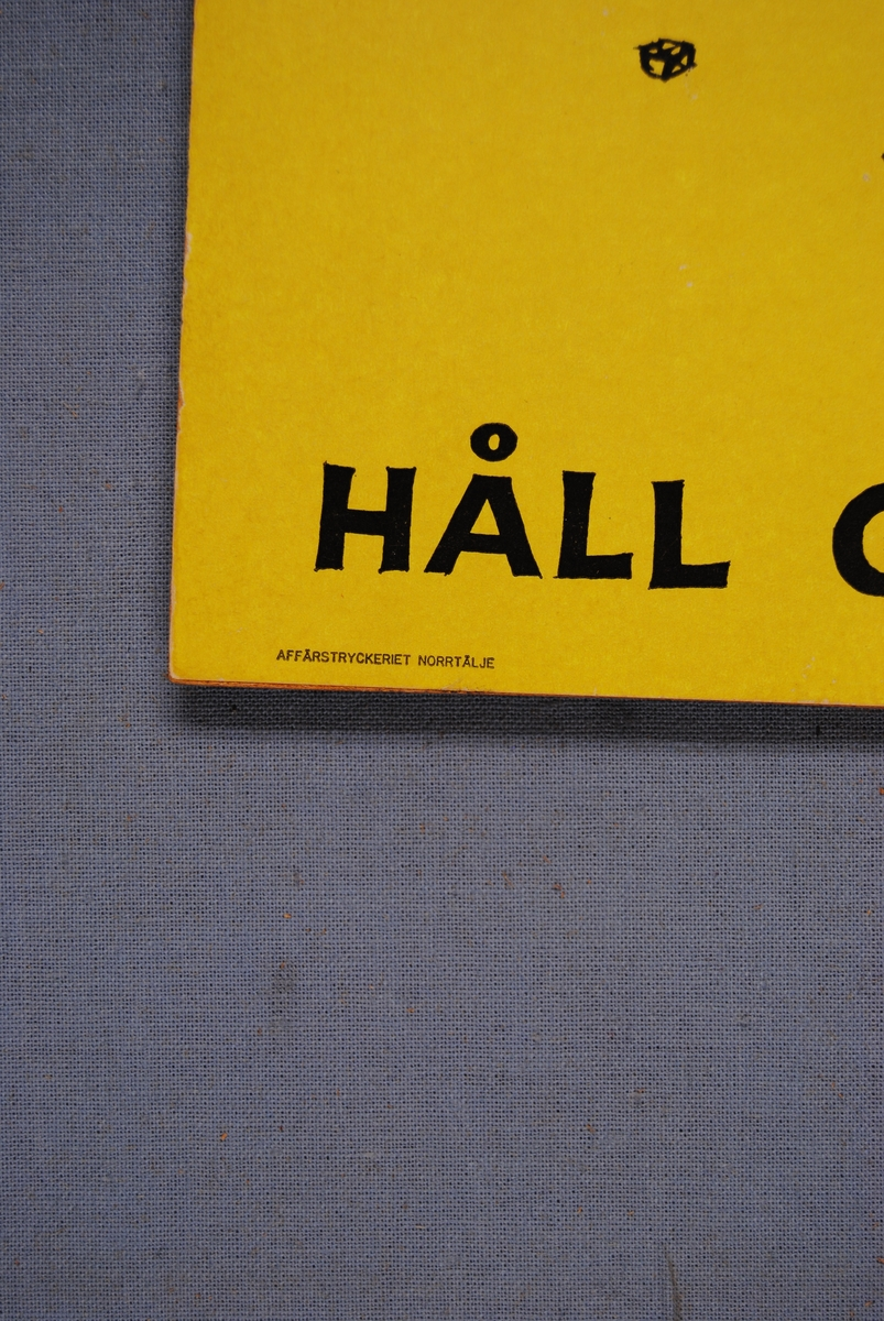 """Påbudsskylt som består av en pappskiva monterad på en träfiberplatta.  Skyltens motiv är en person med blå kläder och blå keps som bär på tre lådor. Personen kan endast kika fram lite bakom lådorna. Runt personens fötter ligger skruvar, spik, muttrar och skärp. Bakgrunden är gul.  Högst upp i påbudsskyltens vänstra hörn finns texten: """"LÅT INTE DETTA BLI ERT FALL..."""". Längst ned finns texten: """"HÅLL GOLVEN RENA"""". Längst ned i vänster hörn står: """"AFFÄRSTRYCKERIET NORRTÄLJE"""". Längst ned i vänster hörn finns texterna: """"CEDERBERG"""" och """"FFA 1009"""". All text är tryckt i svart.   Historik: FFA står för Föreningen för arbetarskydd, som idag (2017) kallas Arbetsmiljöforum. Föreningen bildades 1905 av yrkesinspektören Thorvald Fürst tillsammans med framåtsträvande eldsjälar (bland andra prins Eugén). Föreningen för arbetarskydd startades för att främja ett säkert arbetsliv.   Föreningen för arbetarskydd började arbeta med att förhindra olyckor och dödsfall i industrin. Detta gjordes genom spridning av information, utställningar med skyddsutrustning och utgivningen av den egna tidningen. Det första numret av tidningen kom ut 1913, under namnet """"Arbetarskyddet"""".  Föremålet förvärvades när några av EuroMaints lokaler i Gävle skulle tömmas för uthyrning."""