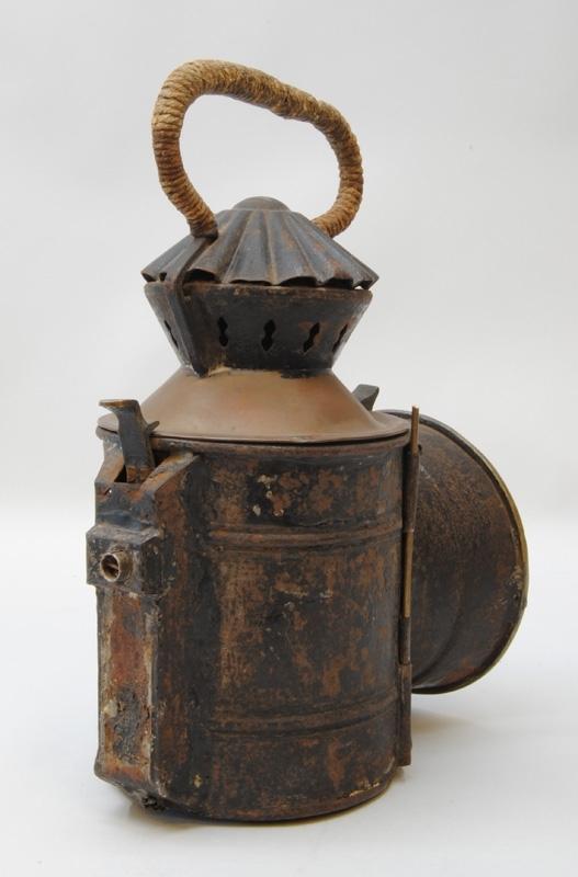"""Handsignallykta, av plåt, cylinderfromad, svartmålad med ett cirkelformat glas. På sidan sitter en skylt med förkortningen """"M.S.J."""" Lyktan kan öppnas framtill vid glaset. Cylindern har ett omålat tak, sedan sitter en del som är genombruten av små syreinsläpp och ovanpå den en veckad """"hatt"""". Allra längst upp sitter ett handtag som är virat med ett snöre av hampa eller annat naturmaterial."""