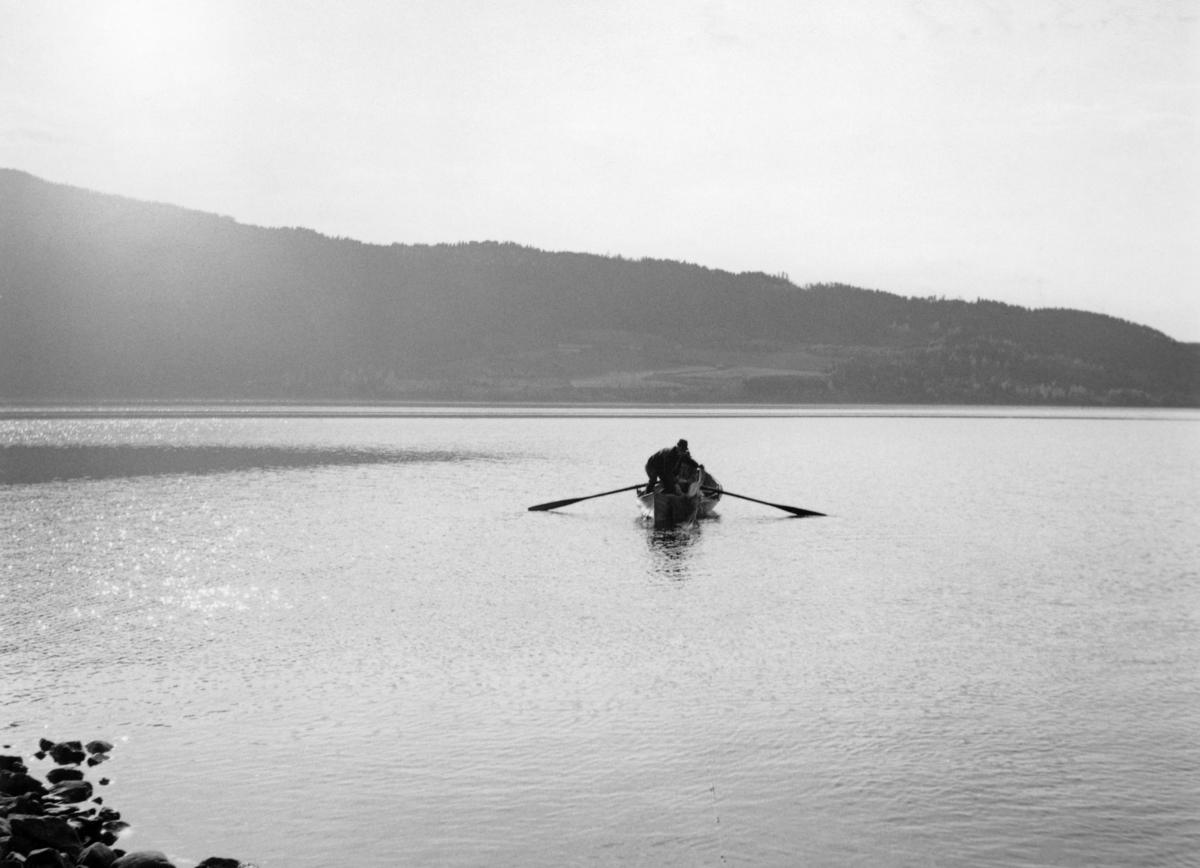Robåt, fotografert i forbindelse med notkast etter krøkle ved Langodden i Furnesfjorden i Mjøsa.  Da dette fotografiet var båten anslagsvis 15-20 meter fra land, og karene i båten var antakelig klare til å kaste den finmaskete krøklenota overbord.  Det ene nottauet befant seg på land, og det andre skulle antakelig ros i land etter at nota var kastet.  Ved inndraing ble den til en U-formet nettpose som fanget opp fisk i den innenforliggende strandsonen.   Notkastet man forberedte her var nok et forsøk med noe som hadde vært et tradisjonelt vårfiske i Furnesfjorden, antakelig fram til disse karenes barndom.  En del større garder hadde hevd på å drive såkalt «langrevfiske», en ferskvannsvariant av linefiske, utenfor sine strandlinjer.  I dette fisket brukte man levende krøkle som agn på langrevens kroker.  Krøkla ble fanget i nøter, som den vi ser på dette fotografiet, når den kom inn mot strendene for å gyte om våren. Denne formen for fiske opphørte etter at det ble forbudt å bruke levende agnfisk.  Karene på fotografiet hadde følgelig neppe vært med på notdraing etter krøkle.  De hadde imidlertid med seg en 90-årig veteran, som nok kunne fortelle hvordan det ble gjort (jfr. SJF-F. 007189).  Denne lokaliteten ved Langodden skal ha vært ett av Mjøsas beste krøklevarp.  Fiskeredskapen var antakelig utlånt fra boet etter brødrene Hans (1900-1966) og Martin (1904-1960) Storihle på garden Stor-Ile i Furnes.  Fra denne garden ble det drevet et omfattende fiske i Mjøsa, til dels med sikte på videresalg av fisk til kjøpmenn på Hamar og i Oslo.  Garden har fortsatt fiskerhytte på Langodden.