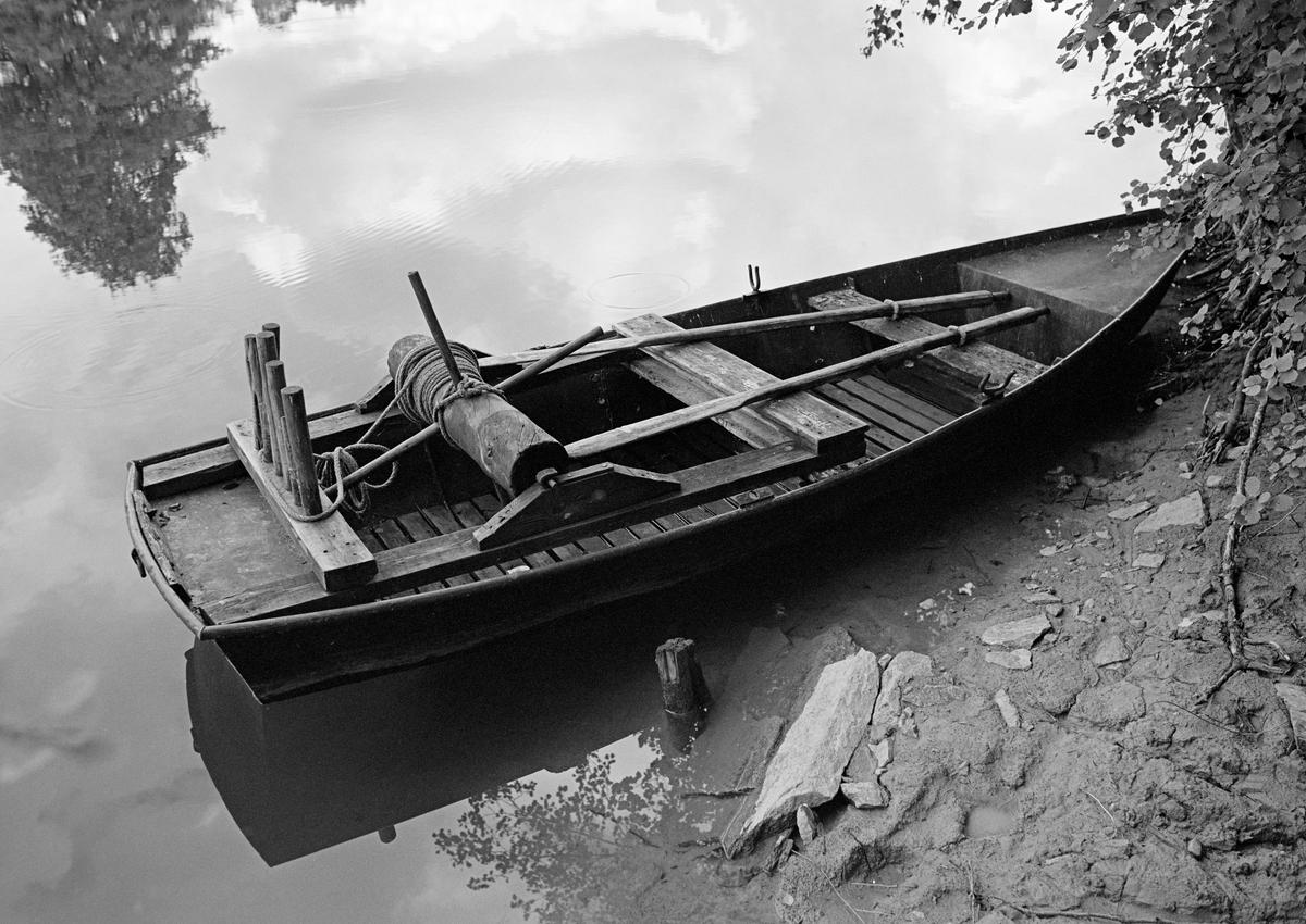 Såkalt «tjoreke» i Haldenvassdraget, fotografert ved en elvebredd i 1982.  Ei eike eller eke er en vanlig betegnelse på en trebåttype som ikke er bygd på en profilert, nedstikkende kjøl, men med et bord som midtakse. I dette tilfellet kan det imidlertid synes som om eka har hud av tynne stålplater.  «Tjor» er betegnelsen på et vindespill som er montert oppi båten, og som ble brukt til å trekke sammen tømmer ved slusene.  Det besto av en horisontal, sylindrisk trekabbe som det var tappet pinner, såkalte «horn» inn i, og viklet 6 millimeters tau rundt.  I begge ender av den nevnte kabben var det tappet inn jernteiner, som ble festet bak J-formete jernbeslag på treklosser oppå den ramma tjoret kvilte på.  Bakerst på den samme ramma, over aktertofta, var det påspikret et kraftig tverrtre med nedtappete pinner.  Tjoret ble brukt til å trekke fløtingstømmer med.  Båtkaren satt da aktervendt i båten og roterte kabben ved å dra hornene på oversida mot seg.  Han kunne også bremse eller låse posisjonen ved å sette beina mot horn på undersida av kabben.  Pinnene akterut ble brukt til å styre vinderetningen med.  Pensjonert direktør Tore Paulsen-Næss fortalte følgende om ekebygginga i et brev han sendte Norsk Skogmuseum med informasjon om ei tjoreke Haldenvassdragets Fellesfløtingsforening overdro til museet (jfr. SJF.07890):  «Fløtningsforeningen hadde egen smed på Ørje fra 1908. I sommerhalvåret arbeidet han som maskinist på et av moseapparatene. Om vinteren bygget han eker og hadde vedlikeholdet av mosemaskinene. Det ble bygget en egen slip som kunne trekke opp moseapparatene for vedlikehold. Smeden var Johan Iversen (1883-1962). Han sluttet ved fylte 70 år 9. 5. 1953, men hjalp til noe i 1954 og i 1955. Nødvendig vedlikehold av de dampdrevne moseapparatene ble utført av andre maskinister. Det var etter hvert anskaffet mindre, motordrevne varpebåter og buntemaskiner. I 1955 ble det ansatt en motorkyndig verkstedformann på Ørje, Kåre Granli (1921-1991). Han påtok seg også byg