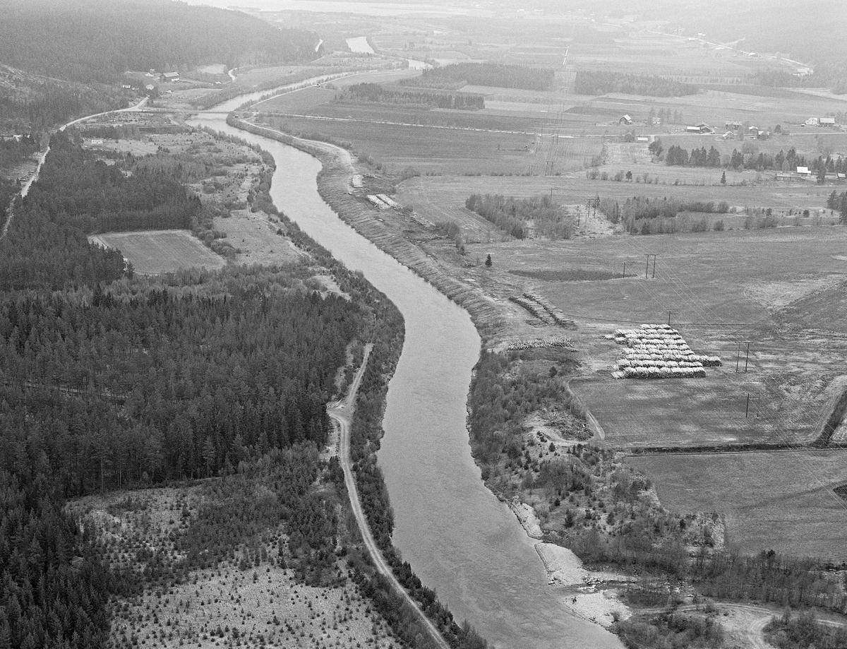 Flyfotografi, tatt over elva Nordre Rena eller Hornsetstrømmen våren 1984.  Til høyre i bildet ser vi Hornsetvelta, en av mange terminalplasser Glomma fellesfløtingsforening fikk bygd etter at et stadig mer finmasket skogsbilvegnett i etterkrigsåra gjorde det mulig å hente tømmer fra skogsområdene med lastebiler.  På denne måten kunne man avvikle fløtinga i de vanskeligste sideelvene.  Terminalplassene muliggjorde også maskinell barking og utislag med bulldosere eller griplastere.  På denne måten kunne man begrense den manuelle innsatsen for å gjøre fløtinga konkurransedyktig.  Fotografiet viser ellers hvordan denne delen av Renavassdraget var blitt kanalisert i etterkrigsåra.  Dette arbeidet ble primært utført for å gjøre det mulig å omdanne våtmarkene langsmed vassdraget til produktive jordbruksarealer.  Landbrukskyndige mente at det dyrkete arealet i redalsbygdebe på denne måten kunne økses med drøyt 10 000 dekar.  For fløtinga var det en fordel at enkelte svinger i den meandrerende elva kunne rettes ut noe.  For fiskets del er det derimot grunn til å anta at kanaliseringa hadde negative effekter.