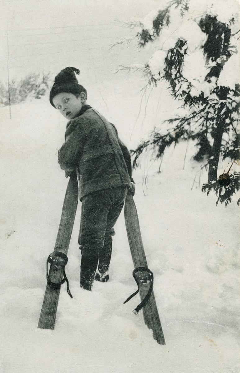 Postkort. Motivet på kortets fremside viser en gutt med ski i vinterlandskap. Skigåing.
