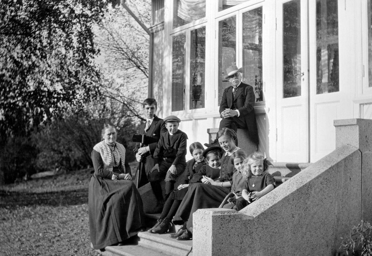 Familiegruppe samlet på trappa mot hagen sør for bestyrerboligen Lund ved Fetsund lenser i Akershus.  Familiegruppa omfatter tre generasjoner.  Dette er antakelig familien til Johs. og Harriet Johannesen, som hadde barna Nils Aars Johannesen, Gudrun Johannesen, Ingeborg Johannesen, Signe Johannesen og Lilly Johannesen.