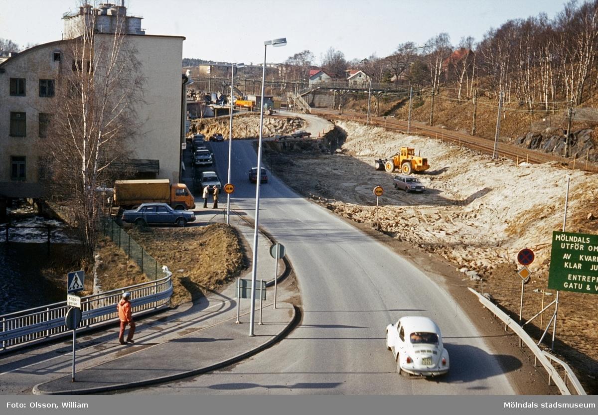 """Vy från Rackarebron västerut, okänt årtal. En vit Volkswagen kör Kvarnbygatan ner. Till vänster ses ett staket och under bron (Royens gata) rinner Mölndalsfallen. Byggnaden är """"Strumpan"""", Kvarnbygatan 10-12, där bilar står parkerade utanför. Till höger pågår vägarbete för att flytta Kvarnbygatan. Längst bort löper Boråsbanan."""