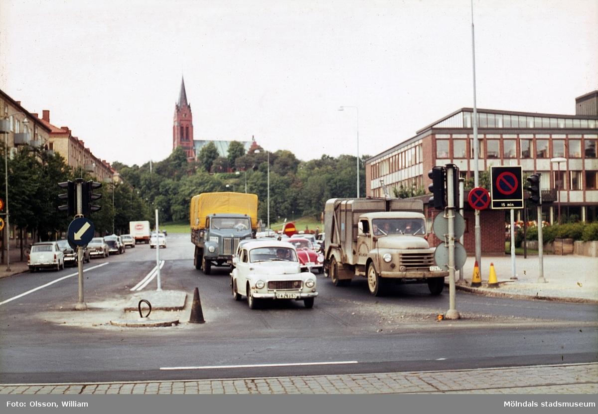 Vy mot Fässbergs kyrka, okänt årtal. Göteborgsvägen ses främst i bild och bilar köar på Tempelgatan (vänstertrafik), för att köra över vägen. Till höger: Mölndals Taxistation och bakom denna skymtar Mölndals stadshus.