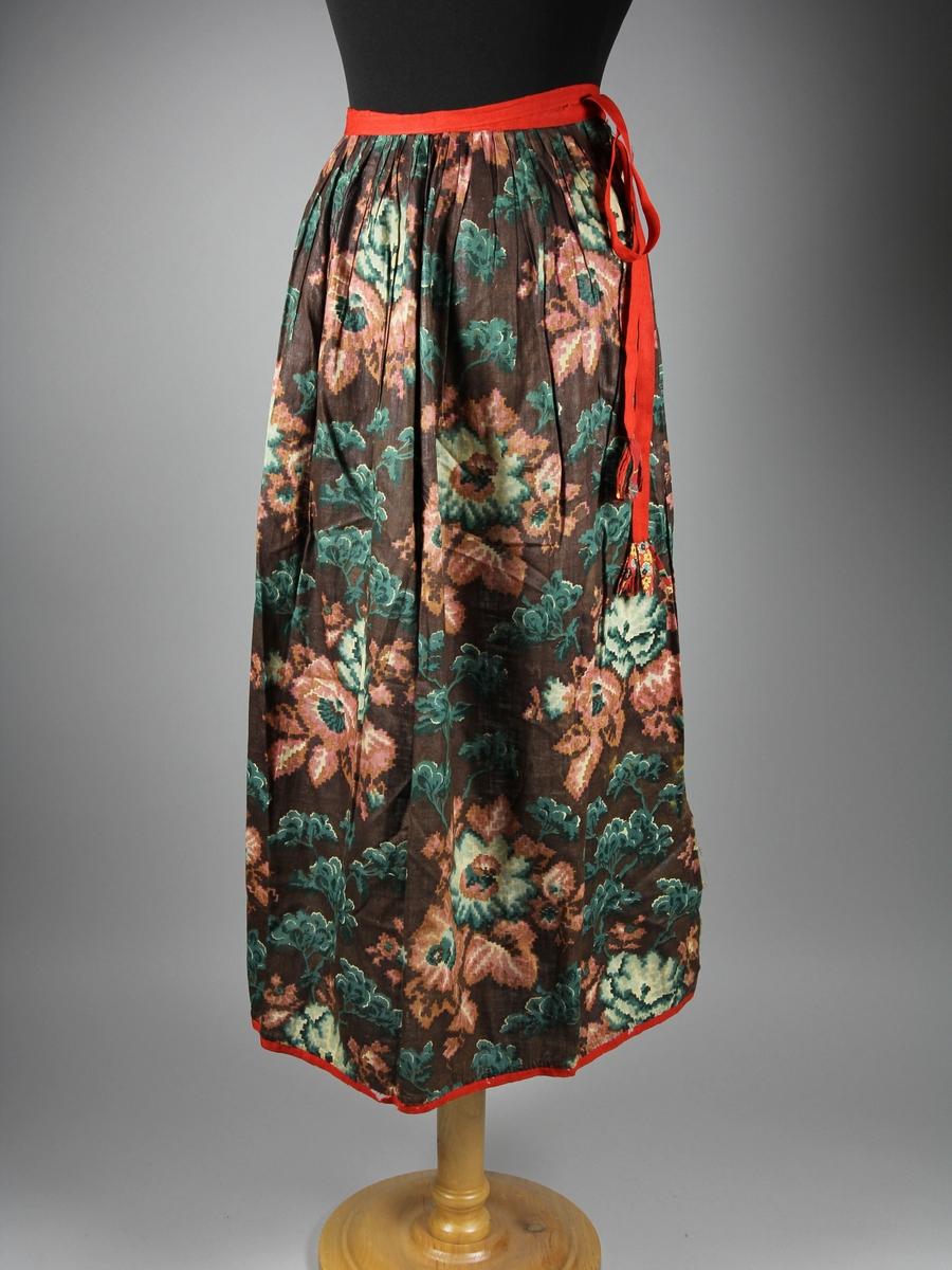 Förkläde av chinntz, stormönstrat och glättat bomullslärft. Mönstret tryckt på tyget i flera färger och föreställer blommor och grenar med löv. Förklädet samlat i rynkor mot ett vävt rött ullband. Samma ullband avslutar nederkanten. Ullbandet är skadat på flera ställen.