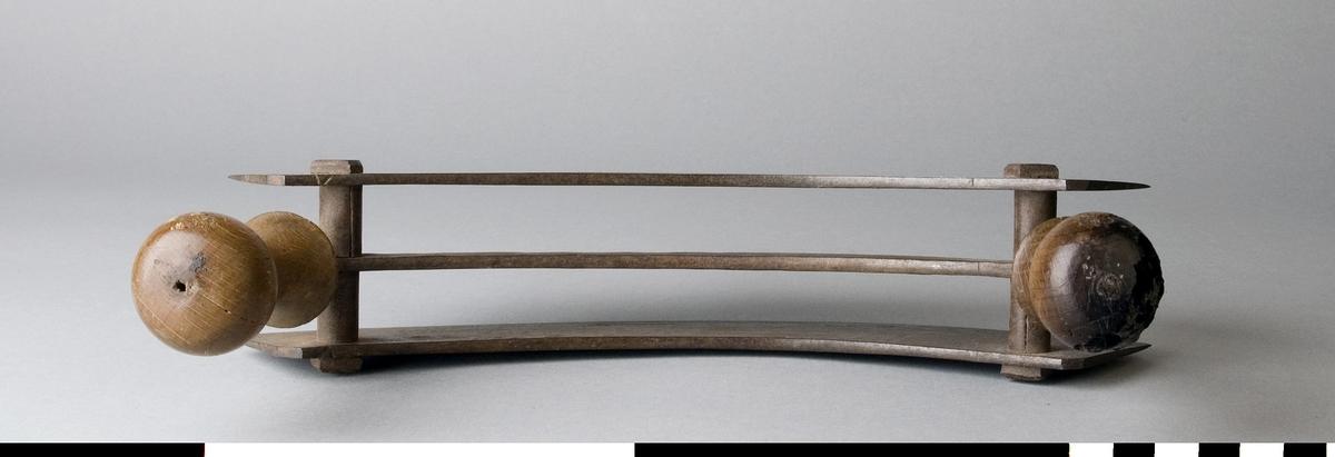 Kniv, dubbelbladig hackkniv, av stål med handtag av trä. De svarvade handtagen sitter på var sin sida av en bygel. De två bladen är fästa i bygeln med bustningar, nitade. I de två bladen är siffrorna 12 instansade.  Ett av trähandtagen är defekt.