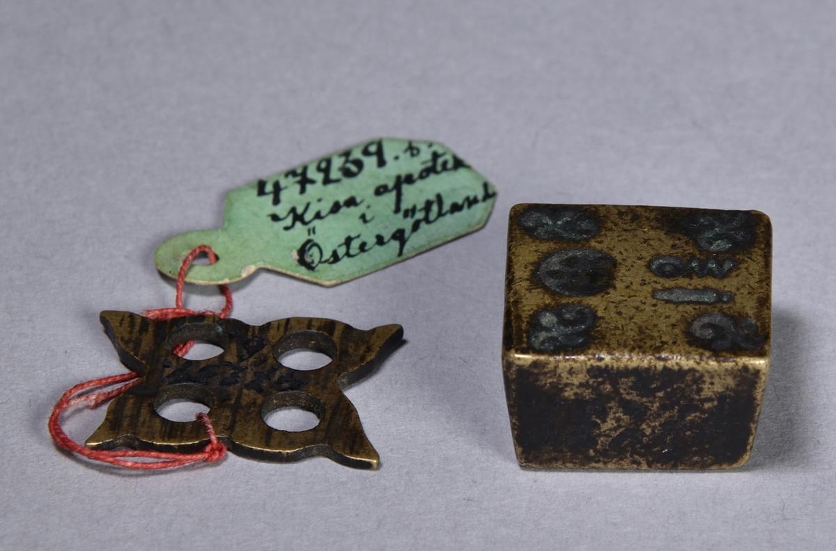 Apoteksvikt av mässing, 2 st. Den ena närmast kvadratisk och den andra genombruten med fyra hål, oregelbunden. Svårtydda stämplar på den kvadratiska vikten.
