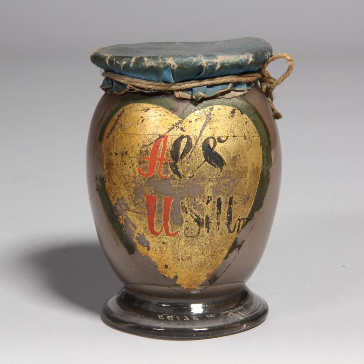 Burk av klart glas. Rundad med utvikt fot, överbundet lock av papper. Två målade etiketter, den ena hjärtformad med text, den andra utan text. Innehåller rester av brunt finfördelat pulver.