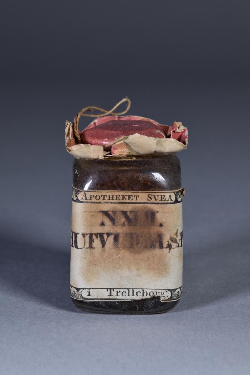 Husapotek i form av en rektangulär trälåda med fällock och bärhandtag av mässing. Lås. Lådfronten nedfällbar och innanför tre små utdragbara lådor. Insida på lådans lock har två utfällbara delar, ihåliga för förvaring samt under dessa fack för glasburkar. I lådan fackindelningen för burkar och flaskor.  De tre små lådorna i fronten innehåller, i en låda medicinalvikter av mässing och en balansvåg med vågskålar av mässing. De mindre vikterna förvaras i svepask av trä. Pappersetikett lådfronten: MEDICINALWIGTAR OCH WICTSKÅLAR. Den andra lådan innehåller tre rektungulära bleckplåtsaskar. Pappersetikett på lådfronten: DIVERSE SALVOR. Den tredje lådan innehåller blyplåster, läkeplåster, mognande plåster och spanska flugplåster. Pappersetikett på lådfronten: DIVERSE PLÅSTER.  I lådan 30 stående flaskor och burkar av glas i olika storlekar. I ett av facken under trälock ligger en samling frön.  Klistrat på lockets insida, de utfällbara delarna, klistrat papper med förteckning över medikamenter respektive underrättelse om medicinalvikter. I den ena utfällbara delen en pappersnota på medikamenter daterad 1815. I den andra utfällbara delen påse med kryddor. Under de utfällbara delarna 8 glasburkar bakom trägaller.