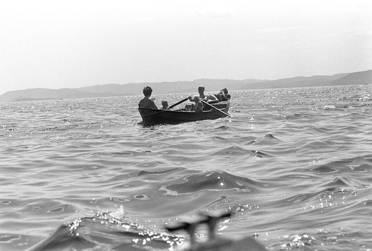 Erik Damman, reklamekonsulent fra Oslo, ferierer i båt med familien i Oslofjorden. De skal ro 10 - 12 mil i løpet av 8 - 10 dager, og går i land på små holmer som fjorden har mange av. Her sitter Erik Damman ved årene. Ragnhild Damman til venstre. Midt i båten Are (8), Brede (5) og Rein (10) helt forut.