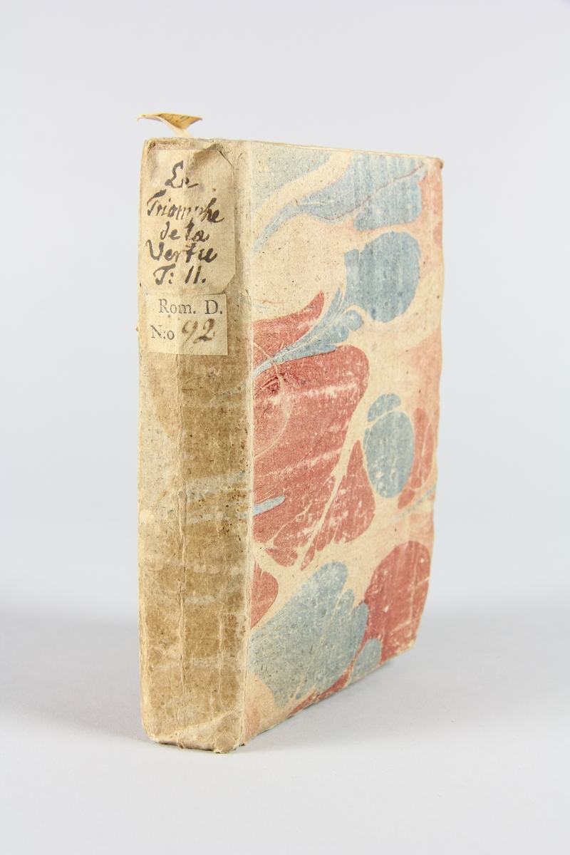 """Bok, häftad """"Le triomphe de la vertu"""", del 2, tryckt 1741 i Haag. Pärm av marmorerat papper, oskuret snitt. På ryggen etikett med titel och samlingsnummer."""