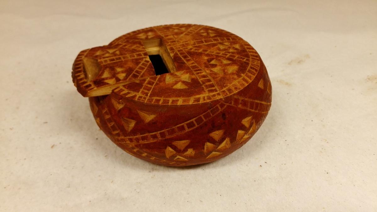 Form: Rund 1 utskaaren æske.  Flattrykt, rund, rødbrunmalt æske av birketræ, utvendig forsirt med karveskurd. Har paa ene side skyvelaag. Diameter 9,5 cm, tykkelse 3,9 cm. Gave fra fru Marie Heiberg, Amble.