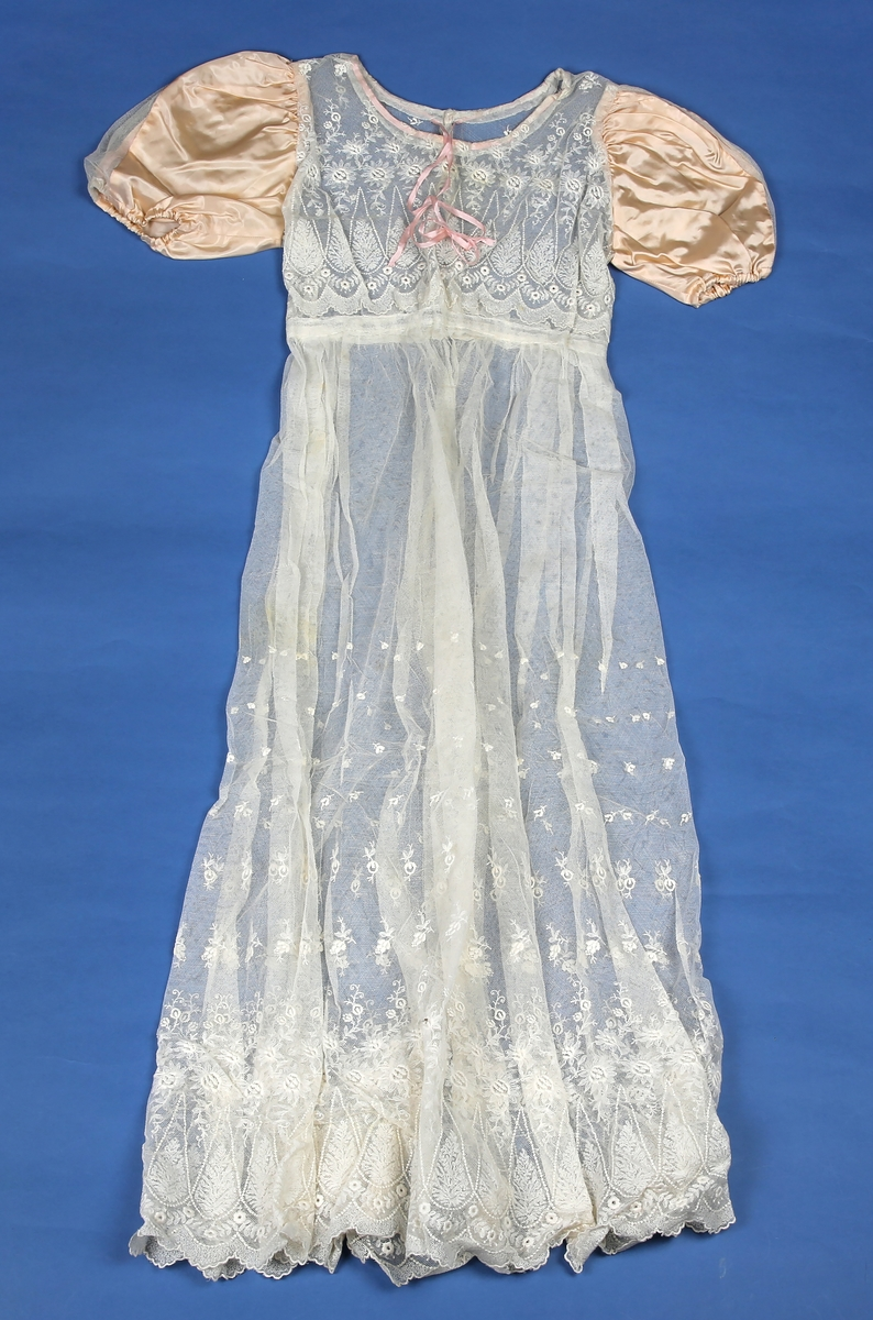 Kjole i tyllblonde med rosa puffermer. Empiresnitt. Snøring i hals med rosa bånd. Trykknapper i rygg.