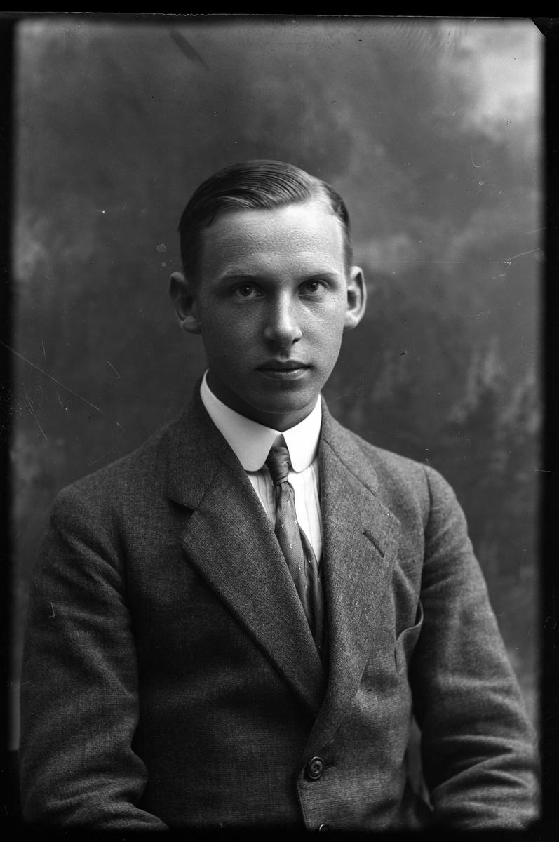 Porträtt av Gösta Bennert i kavaj, vit skjorta och slips.