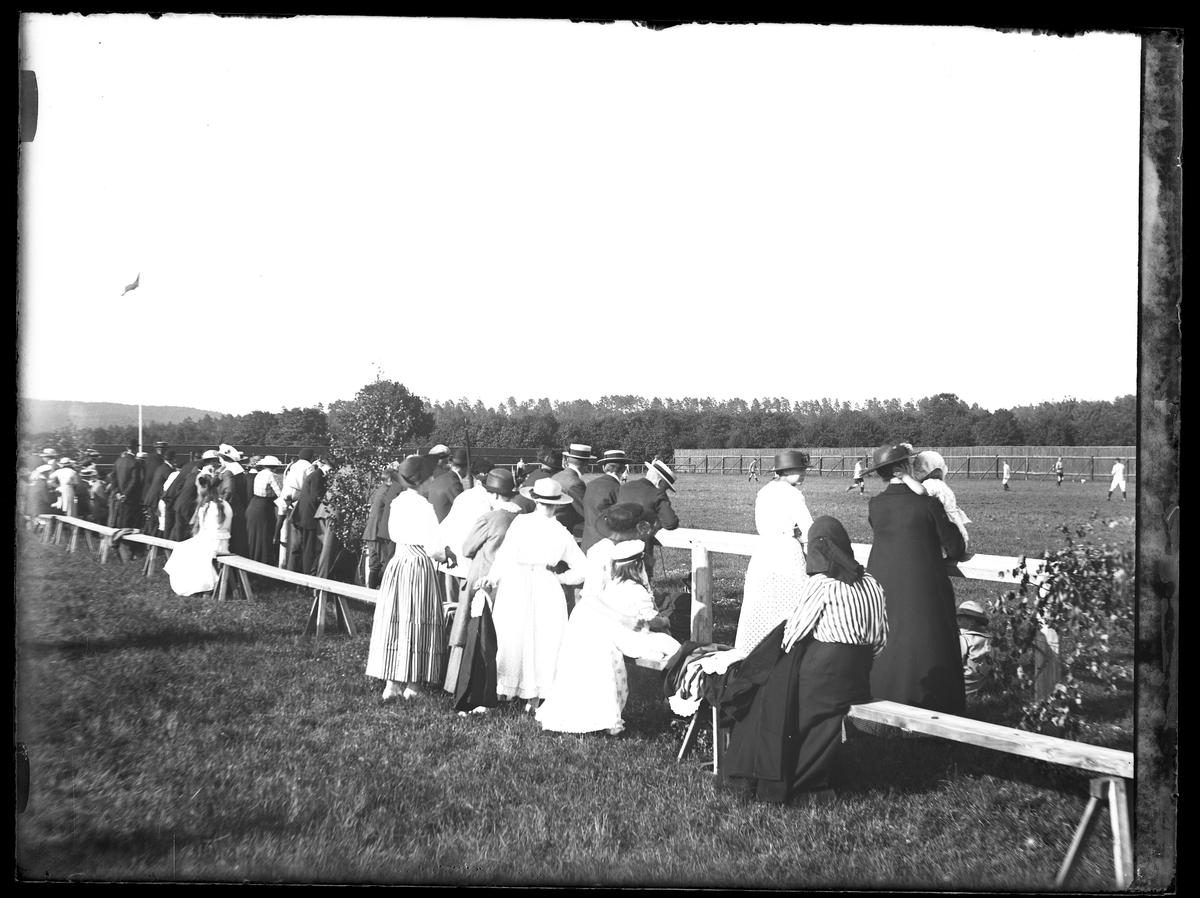 Sommarklädda åskådare tittar på en fotbollsmatch på idrottsplatsen.