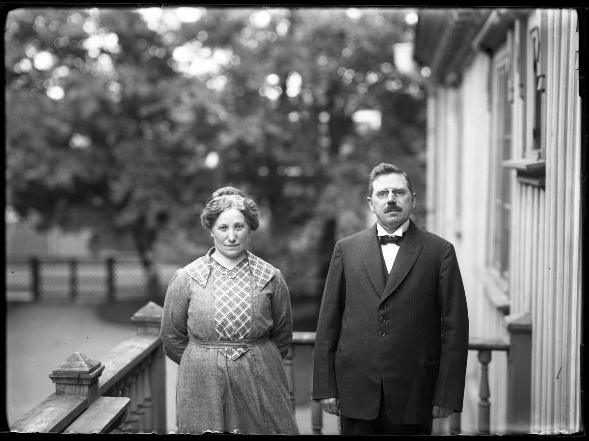 """Herr och fru Petersén porträtterade sida vid sida på en balkong eller veranda. I fotografens beskrivning står """"Hr. Petersén m. fru"""" men skulle kunna vara Petrus Wilhelm Pettersén, kontorist vid Alingsås Bomullsväveri, och hans fru Anna Johanna Boman."""