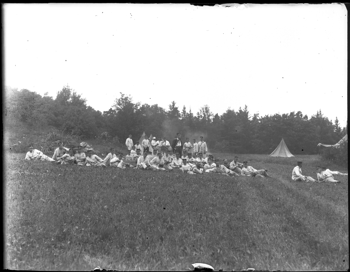 Gruppbild tagen under fotografen Harald Olssons excercistid. Ett stort antal män står eller ligger i gräset vid en lägerplats. I bakgrunden syns tält.