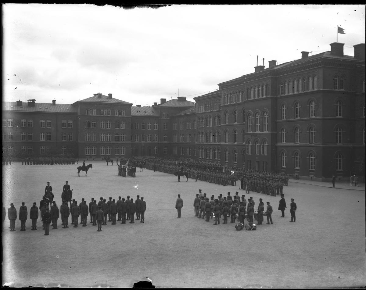 Uniformerade militärer uppställda på gårdsplan utanför garnisonsbyggnaden. Gruppbild tagen under fotografen Harald Olssons excercistid.