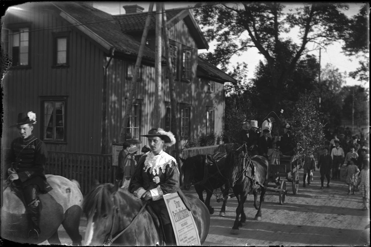 """Två utklädda män kommer ridande, efter dem kommer två hästar med vagn samt ett antal promenerande människor. I fotografens egna anteckningar står det """"Jazzkapellet A.I.F.s fest"""""""