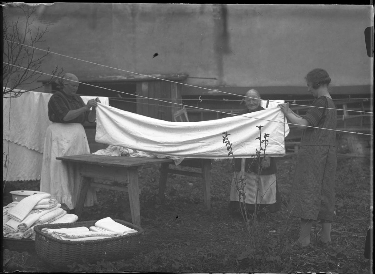 Tre kvinnor tar hand om torr tvätt vid en tvättlina. Två av dem hjälps åt att dra och vika ett lakan. Bredvid dem står två korgar fulla med färdigvikt vittvätt.