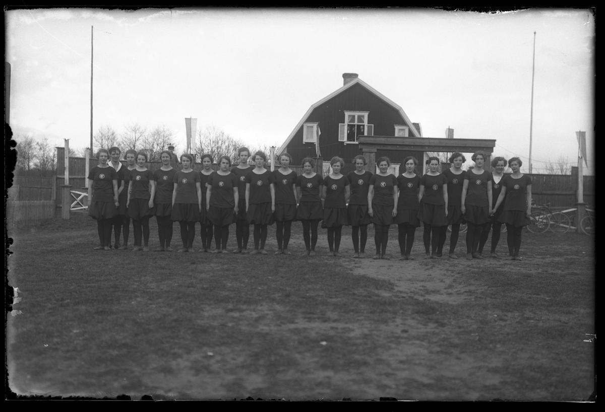 Gruppbild på Alingsås Idrottsförenings (AIFs) kvinnliga trupp i svarta dräkter. Bilden är tagen i samband med en gymnastikuppvisning. I övervåningens fönster på villan i bakgrunden tittar tre män ut.