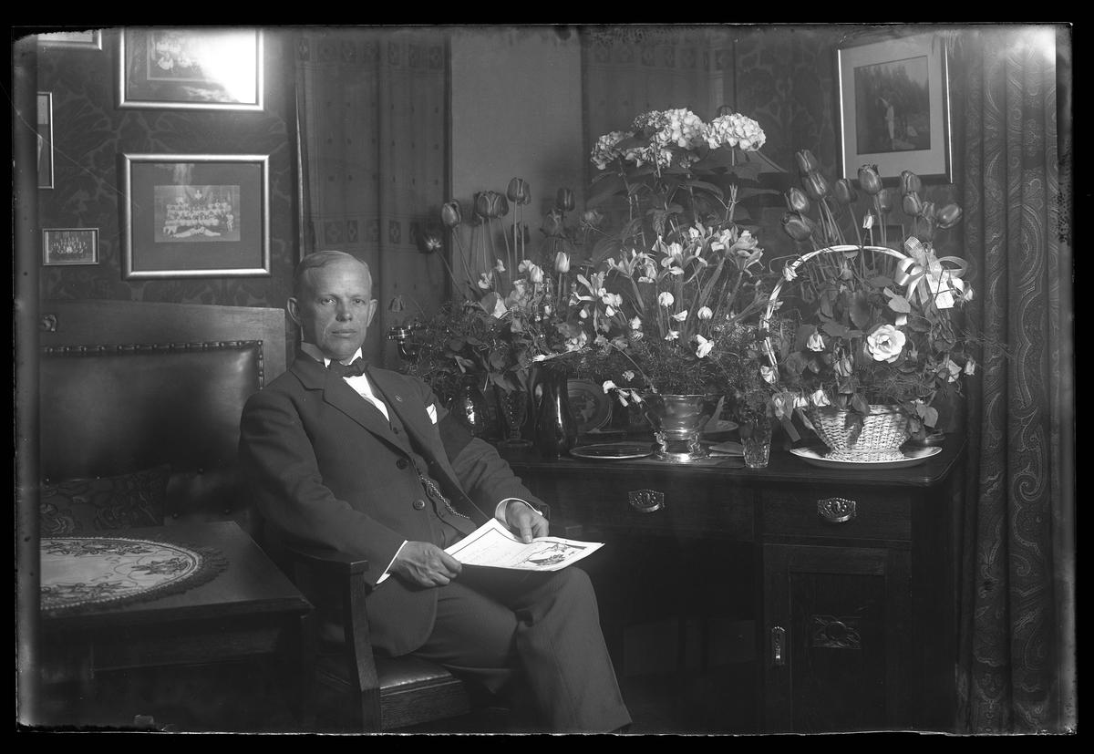 Hjalmar Nilsson fotograferad omgiven av blommor i samband med sin 40årsdag. I handen håller han ett telegram.