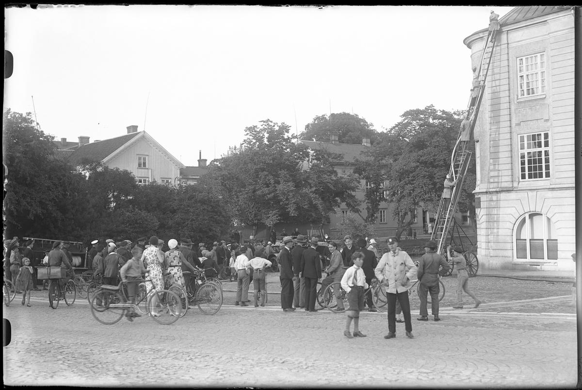 Fyra brandmän står på en stege. Stegen står lutad mot gamla Sparbankshuset på Lilla torget och nere på torget står ett stort antal åskådare och tittar.