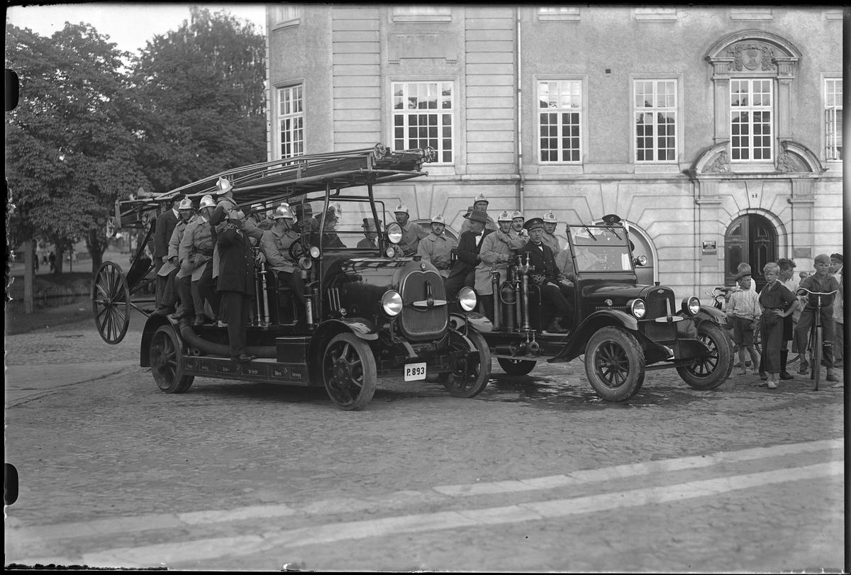 Två brandbilar med uniformsklädda brandmän i står parkerade på Lilla torget, framför gamla Sparbankshuset. Bredvid dem står några pojkar med cyklar.