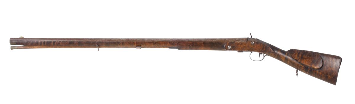 Armégevär. Flintlåsgevär ändrat till slaglåsgevär av armétyp. Det har helstock med näsbeslag av horn. Även laddstockens tjocka ände är tillverkat av horn. Kolven har en bakplåt av stål och utskuret kindstöd. Pipan är rund och har ett filat gropsikte framför svansskruven, och ett avlångt mässingskorn i framkanten. Bärremsbeslagen sitter vid mellanrörkan och vid kolvens underkant, strax bakom varbygelbeslagen. Pipan är slätborrad och har en innerdiameter på 20 mm. Inskrivet i huvudkatalog 1944.