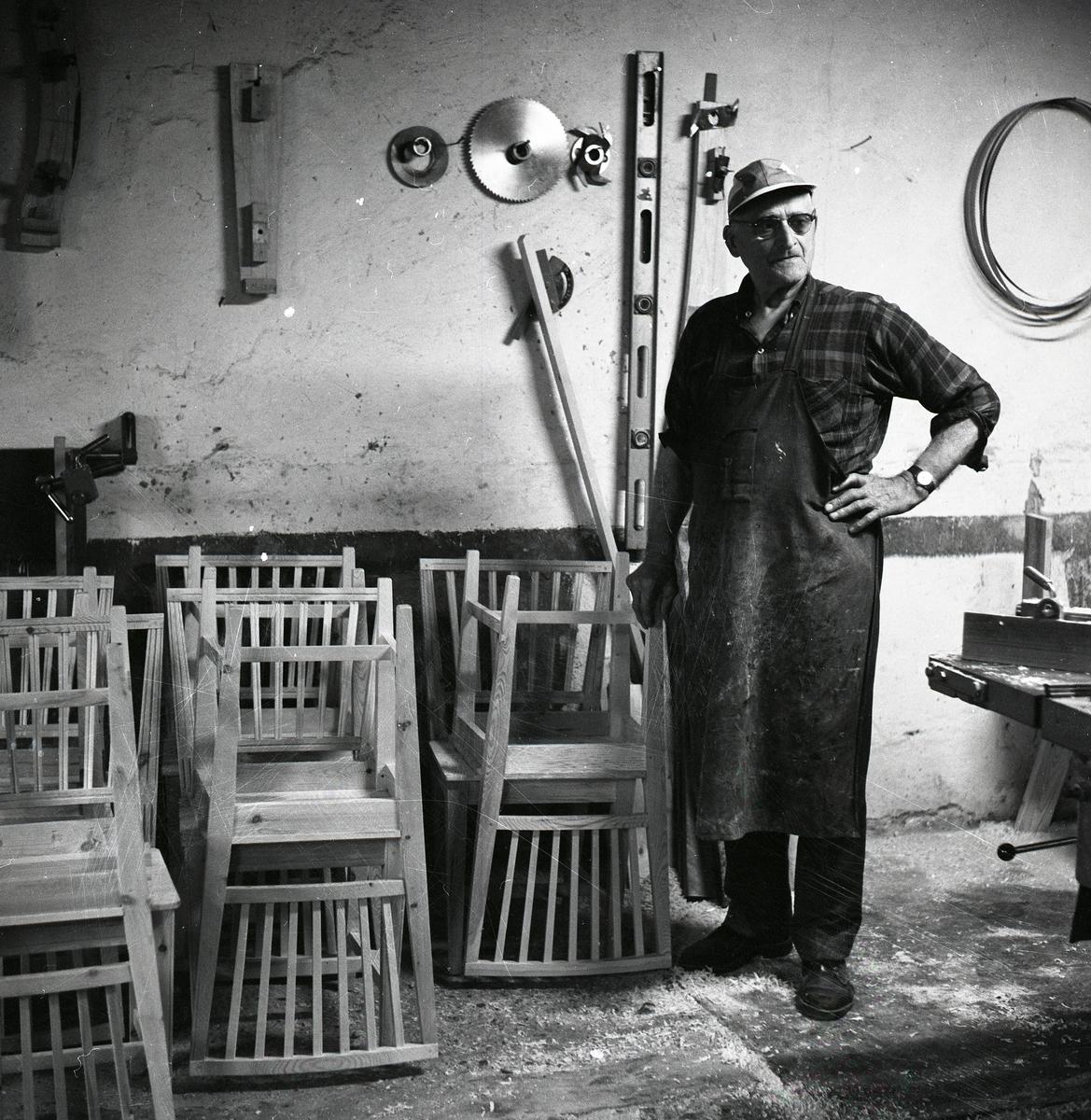 En man i förkläde och keps står bredvid några stolar i en verkstad, 1968.