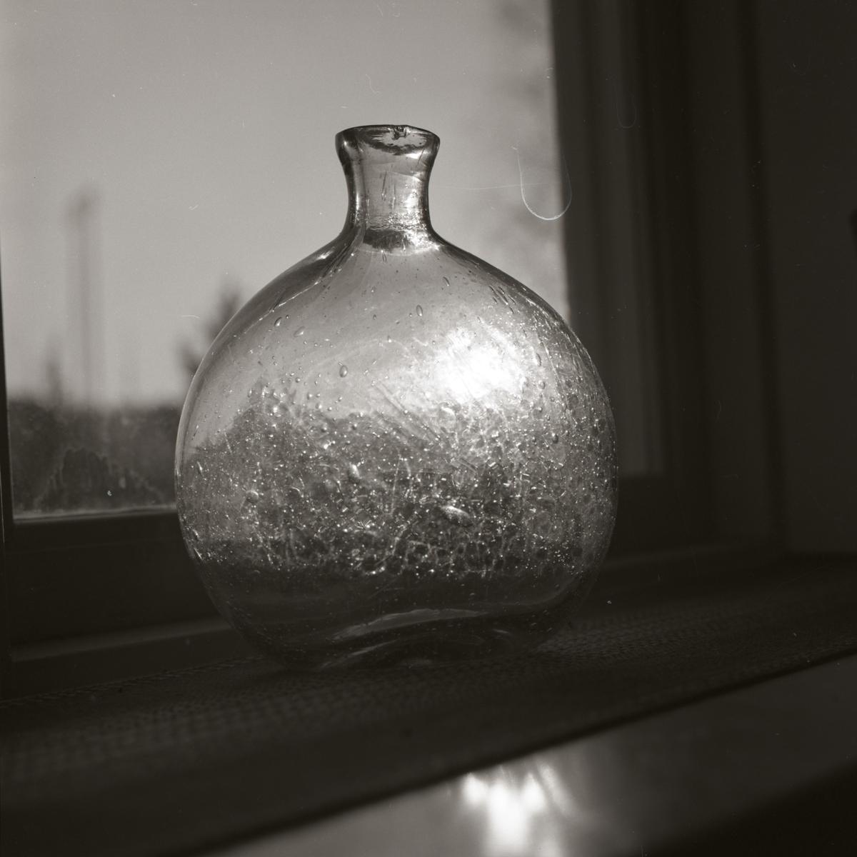 En rund glasflaska står i en fönsterkarm och solljuset reflekteras genom glaset, 1968-1969.