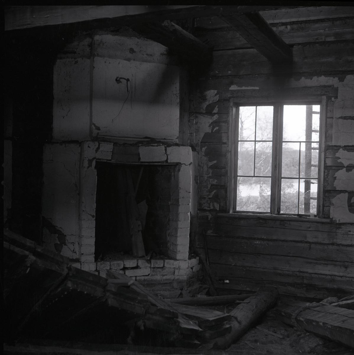 Ett nedgånget rum med en öppen spis i ett hus i Rengsjö.