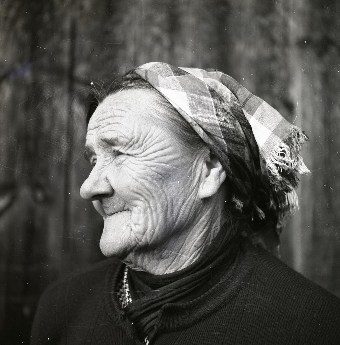 Porträtt av en äldre kvinna med rynkigt ansikte och rutig sjalett runt håret.