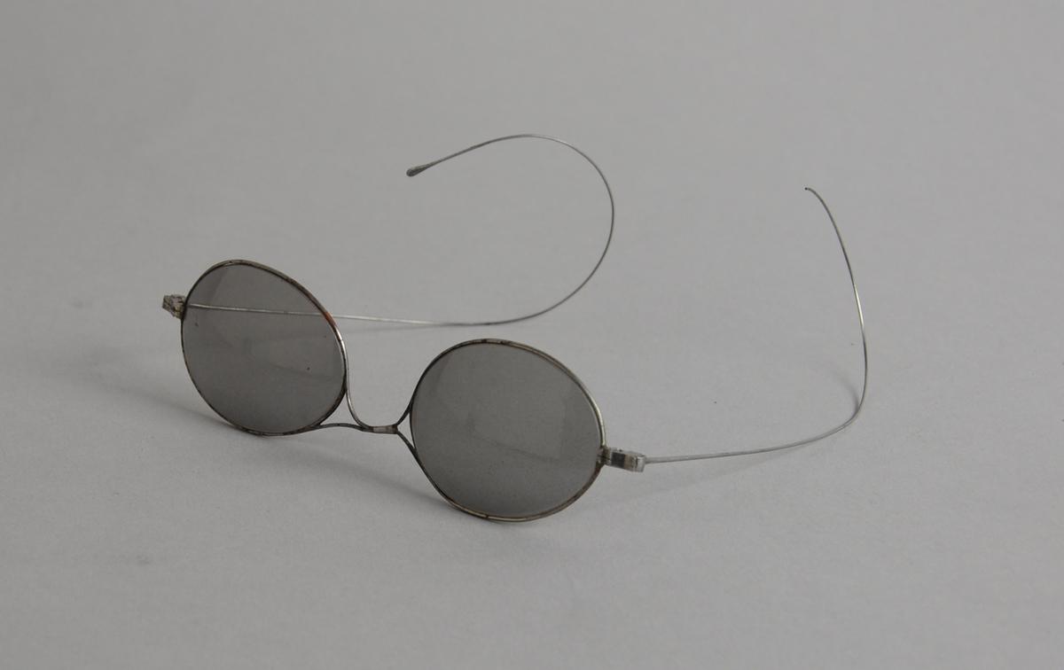 Solbriller med ovale mørke glass og metallinnfatning, med tynne metallbøyler.