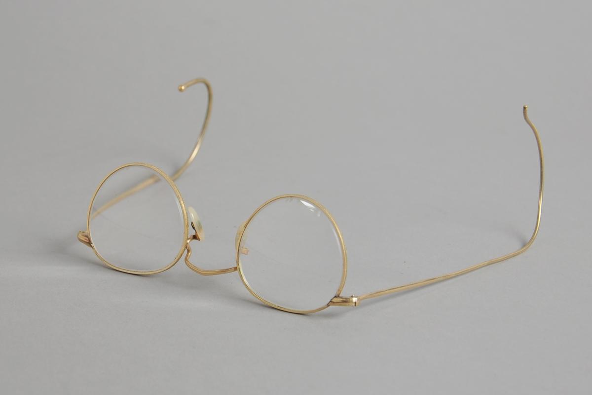 Brillen har tilnærmet sirkelrunde glass med sterk pluss-styrke, og gullfarget metallinnfatning og stenger som er buede ytterst.