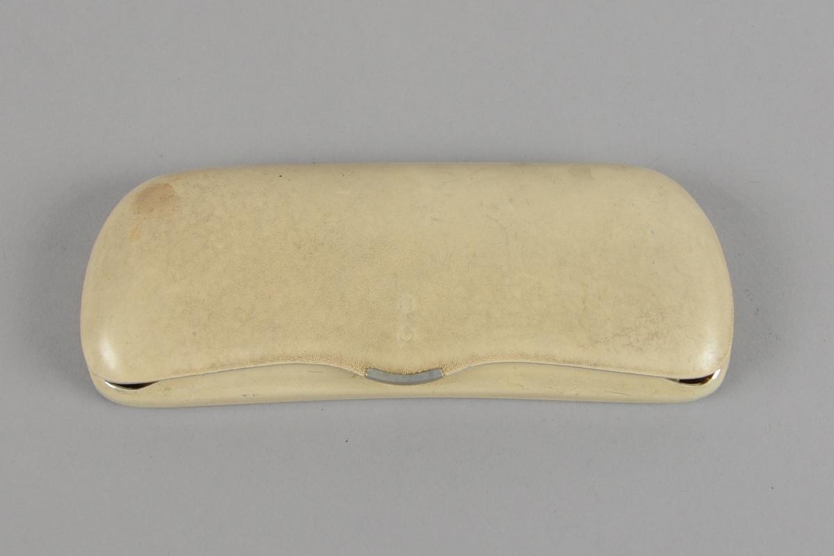 Brilleetui av hvit hardplast med fór av filt. Etuiet åpnes på langsiden med kneppelås. I etuiet ligger det en gul pusseklut og to avisutklipp.