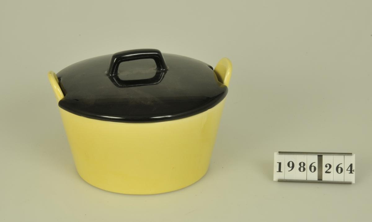 Byttan är gulglaserad. Locket svartglaserat. Botten märkt: 4303 Diam. 130 mm. Lockets diam: 135 mm.
