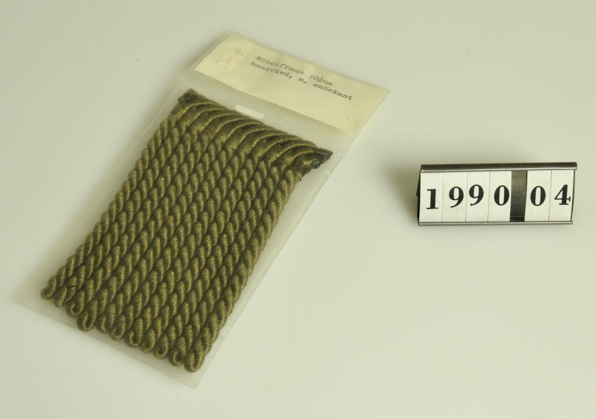 Grönmelerad. Förvaras i plastförpackning med text: Möbelfrans 10 1/2 handvävd, med snörkant.