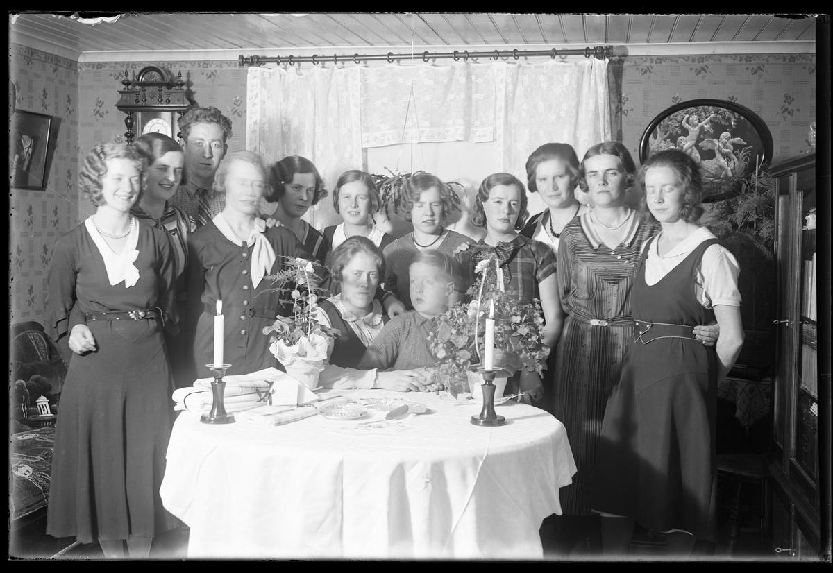 """Elva kvinnor, en man och en pojke är samlade runt ett bord. På bordet ligger en vit duk och två ljus är tända. I fotografens anteckningar står det """"Antonssons, Vadsjön""""."""