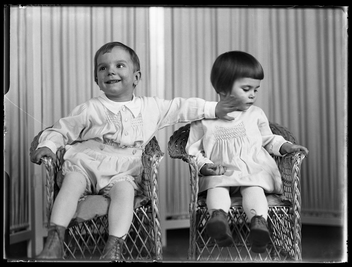 """En pojke och en flicka sitter i varsin korgstol. Pojken klappar sin syster på kinden. I fotografens anteckningar står det """"Ing.[enjör] Bergs barn"""", tolkat som tvillingarna Peter Wilhelm och Ulla Maria."""