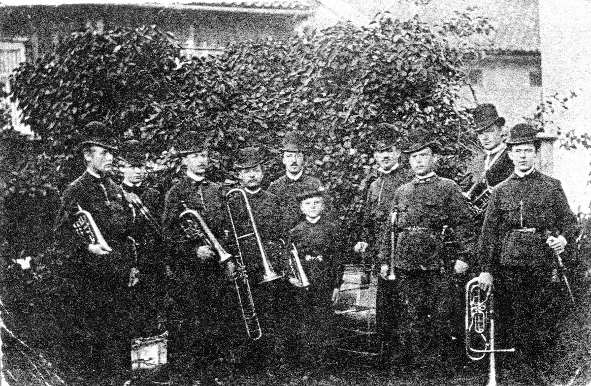 Gruppbild med 9 män samt 1 pojke, tillhörande gamla Skarpskyttekåren, stående med var sitt musikinstrument. Musiken vid Alingsås.