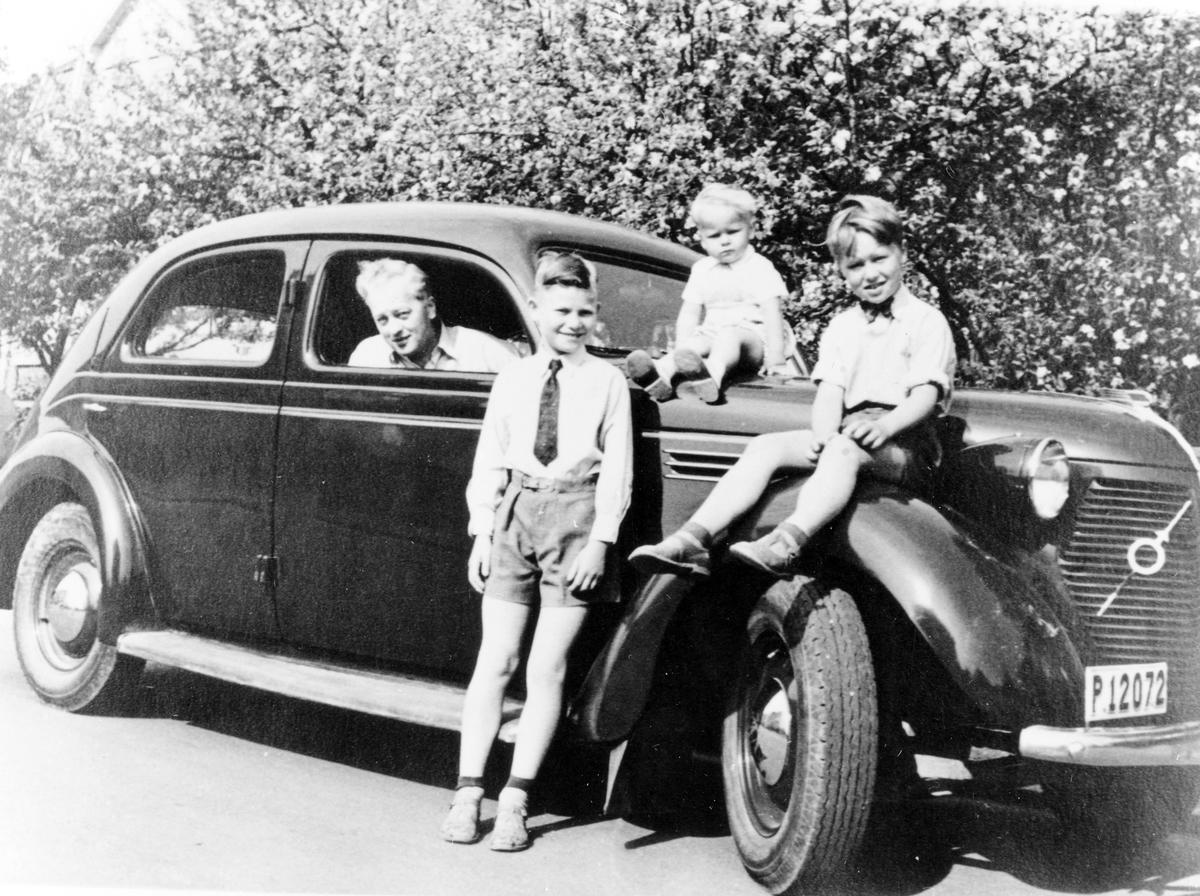 Nils Sahl sitter i sin första bil, en Volvo 1939, registreringsnummer P12072. Två av Nils söner sitter på bilen medan en lutar sig mot den.  Bilen användes under 1950-talet.
