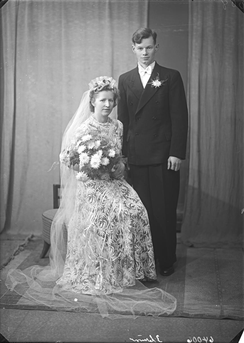 Portrett. Brudebilde. Ung kvinne i lys blomstermønstret kjole med slør og ung mann i mørk dress. Brudepar. Bestilt av Hr. Berht Berthsen. Haugeveien 52
