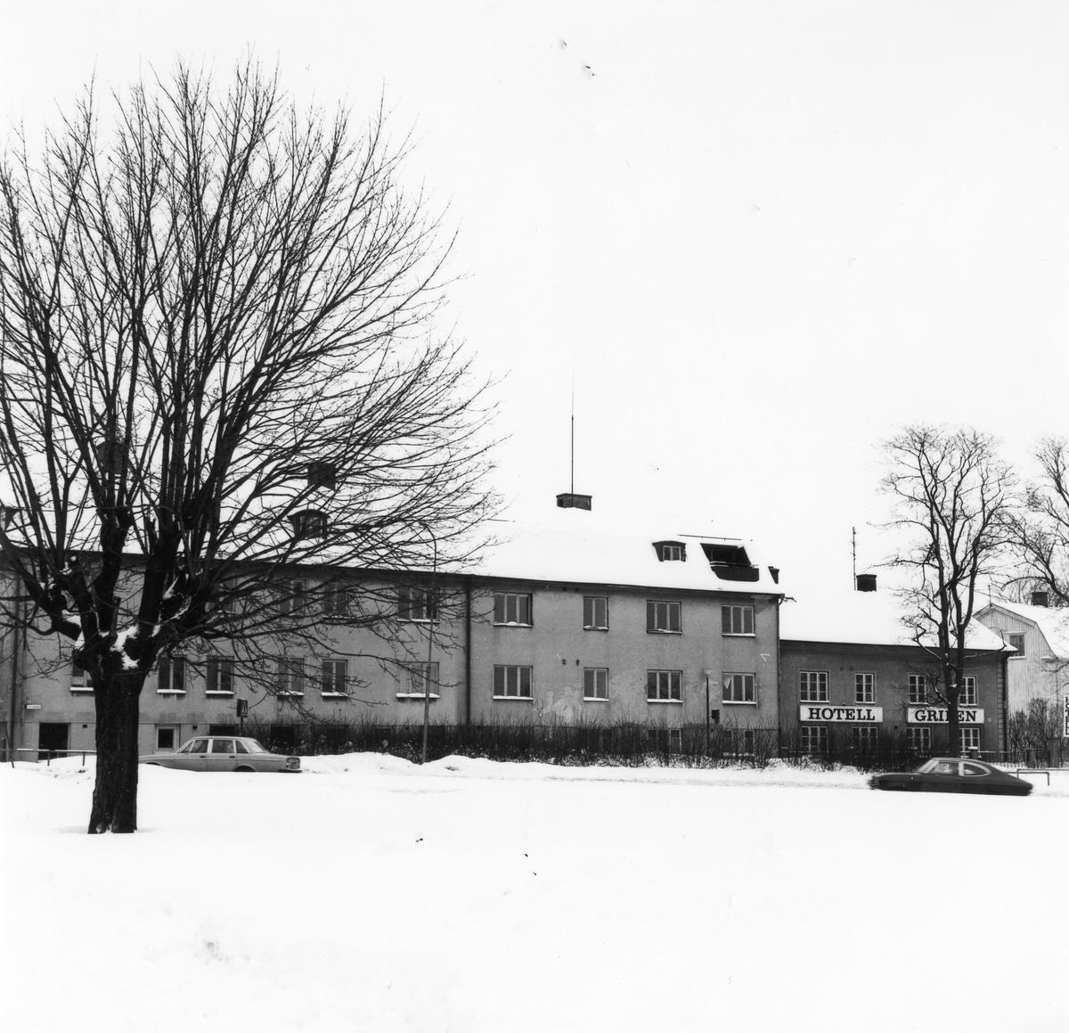 Vinterbild korsningen Kungsgatan och Vänersborgsvägen med ett 2 vånings bostadshus i centrum på bild.  Bostadshus i två våningar med butikslokaler i källarplan utmed Kungsgatan. Entrépartier mot gårdssidan. Putsade väggar, tvåkupigt taktegel. Lägenheter försedda med kakelugn i ett rum. Parkettgolv.Beslut om rivning i november 1978. Fastighetägare: Alingsås kommun.