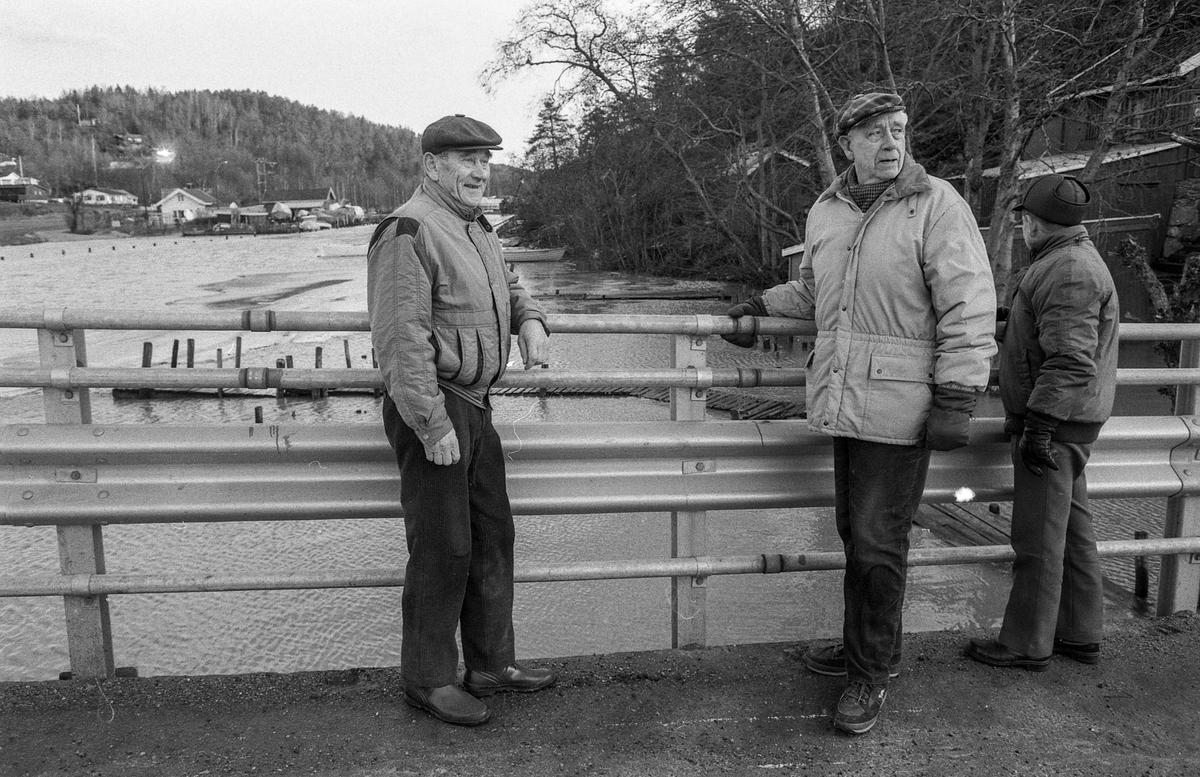 Flom ved marinaen i Son. Sjøen går opp til brygga og over trapper og gjerder. Tre menn ser på. Karlsen, Jacobsen og Hansen.