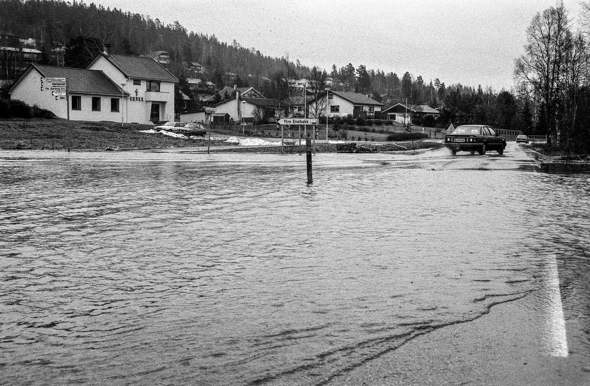 Flomskader på veiene, Riksvei 120, Ytre Enebakk. Vannet flommer over veier og jorder, biler kjører så vannspruten står.
