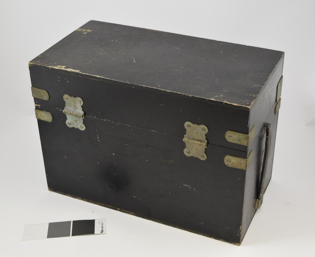 Sort kasse i tre, høy rektangulær med metallbeslag i hjørnene. Lukkemekanisme påfestet foran. Håndtak i skinn på venstre side. Inneholder rund lykt med håndtak og ledning.