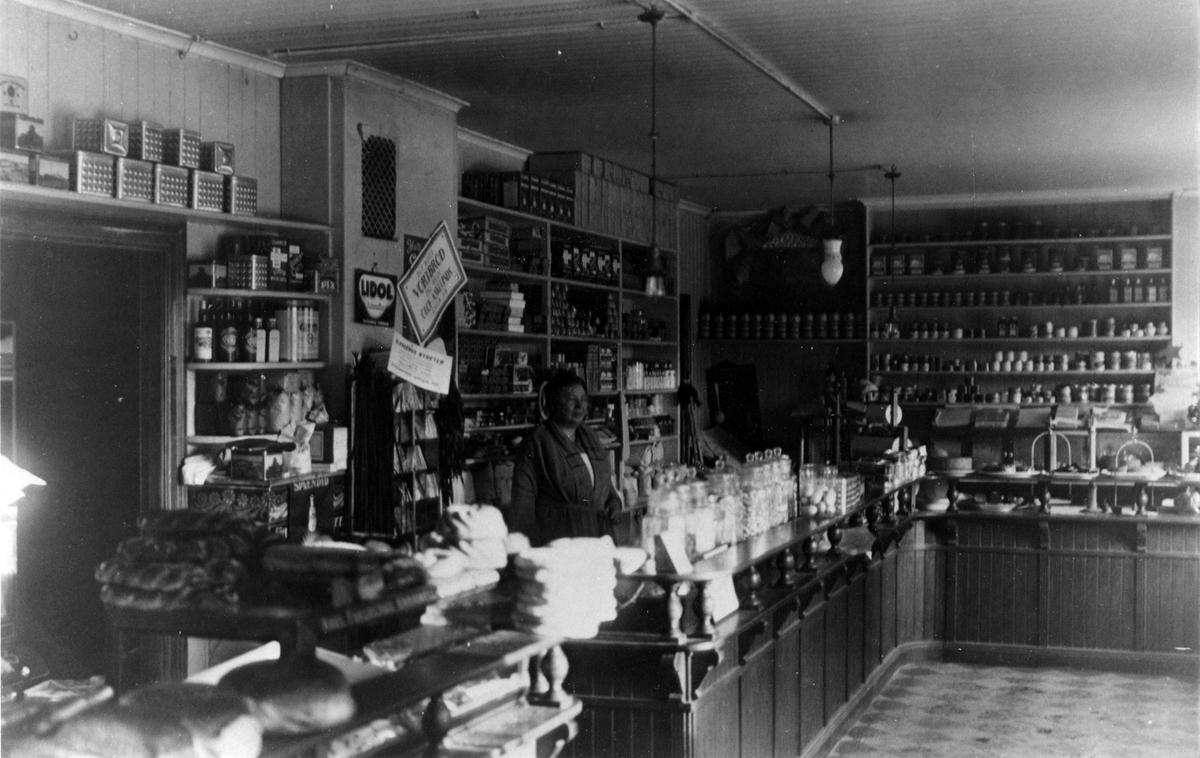 Inifrån K.P. Wessmans speceriaffär. En överblick av hyllor med livsmedel av alla dess slag. Bakom disken står en kvinna.
